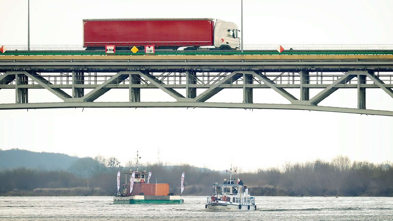 Widok na samochód ciężarowy jadący mostem nad Wisłą. Poniżej płynie barka i mały statek.